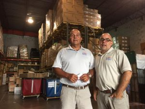 Rafael Landa (left) and Pedro Behrens, who run the Doral shipping firm Letterr Express, in front of medical shipments bound for families in Venezuela. PHOTO CREDIT: Tim Padgett WLRN.org)